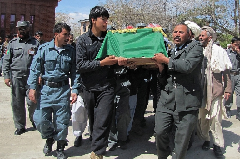 <p>Afghan men carry the coffins of police officers who were killed in a roadside bomb ambush in Ghani province on April 28, 2013.</p>