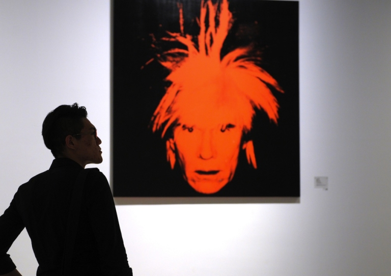 <p>A visitor looks at a retrospective of works by American pop artist Andy Warhol at the Shanghai Power Station of Art museum on April 28, 2013.</p>