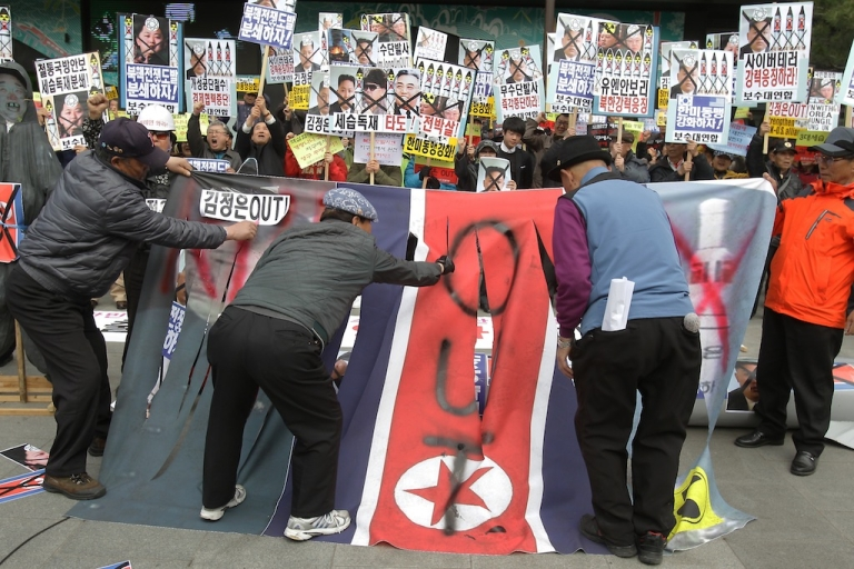<p>South Korean protesters deface a North Korean flag during a rally against North Korea on April 15, 2013 in Seoul, South Korea.</p>