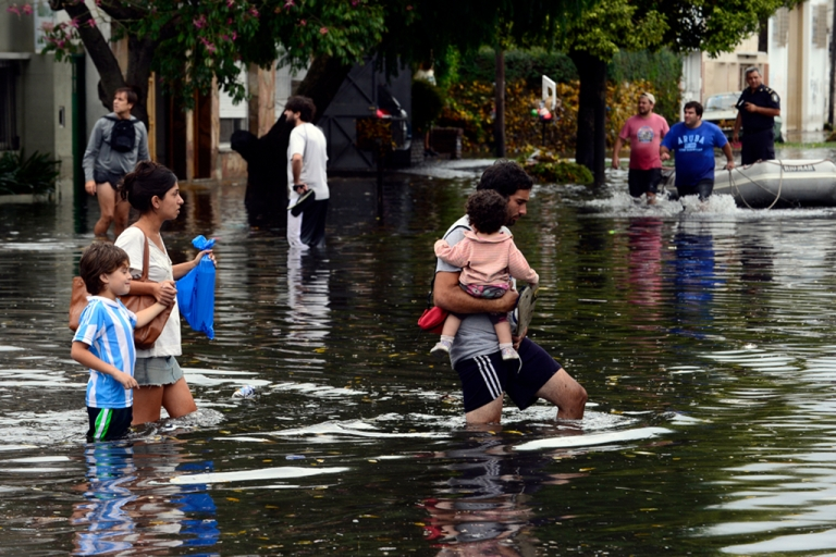 <p>People wade through flooded streets as the water starts subsiding in La Plata, located 63 km south of Buenos Aires, on Apr. 3, 2013 after a powerful storm pummeled the Argentine capital overnight from Tuesday to Wednesday.</p>