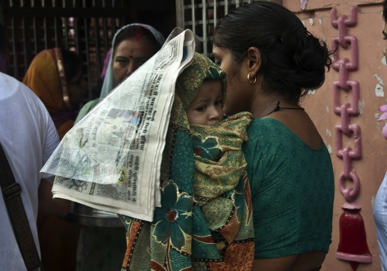 <p>An Indian woman covers her baby with a newspaper as she waits in line to offer prayers at the Gauri Shankar Temple in New Delhi on July 9, 2012.</p>