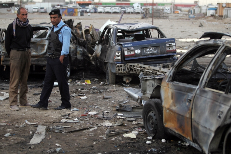 <p>An Iraqi policeman and civilian inspect the site of a car bomb attack that took place the previous day in Baghdad's district of Sadr City on April 16, 2013. Dozens of attacks across Iraq, including a brazen car bombing on the way to Baghdad airport, struck just days before the country's first elections since US troops withdrew.</p>
