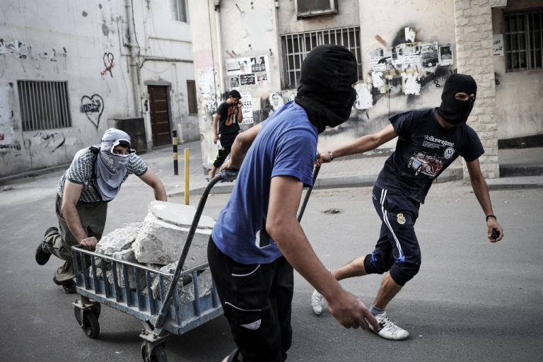 <p>Bahraini protesters use a trolley to carry bricks during clashes with riot police following a protest against the Formula One Grand Prix on April 19, 2013 in the village of Sanabis, west of Manama.</p>