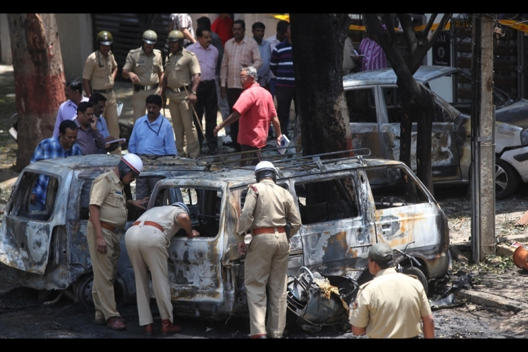 <p>Indian police search for evidence inside burned vehicles following a blast near the Bharatiya Janata Party (BJP) office in Bangalore on April 17, 2013. Police in the southern city of Bangalore said Wednesday they were investigating a minor blast outside the office of a political party which injured 12 people.</p>