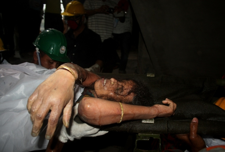 <p>Bangladeshi rescuers carry a survivor who was recovered, on April 27, 2013 in Savar, three days after an eight-storey building collapsed. Bangladesh made a string of arrests today over the collapse of a factory complex which killed at least 351 people as exhausted rescuers battled to find more survivors among the corpses.</p>