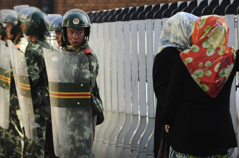 <p>An ethnic Uigur women look through a security fence to the Grand Bazaar which remains closed as Chinese soldiers look on in Urumqi, in China's farwest Xinjiang region on July 9, 2009.</p>