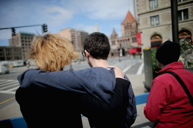 <p>People embrace before a moment of silence honoring the Boston Marathon bombing victims in Copley Square, near the bombing sites, on April 22, 2013 in Boston, Massachusetts.</p>