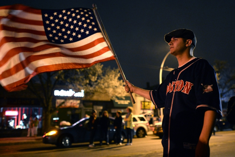 <p>A man waves the US flag after the capture of the second of two suspects wanted in the Boston Marathon bombings April 19, 2013 in Watertown, Massachusetts.</p>