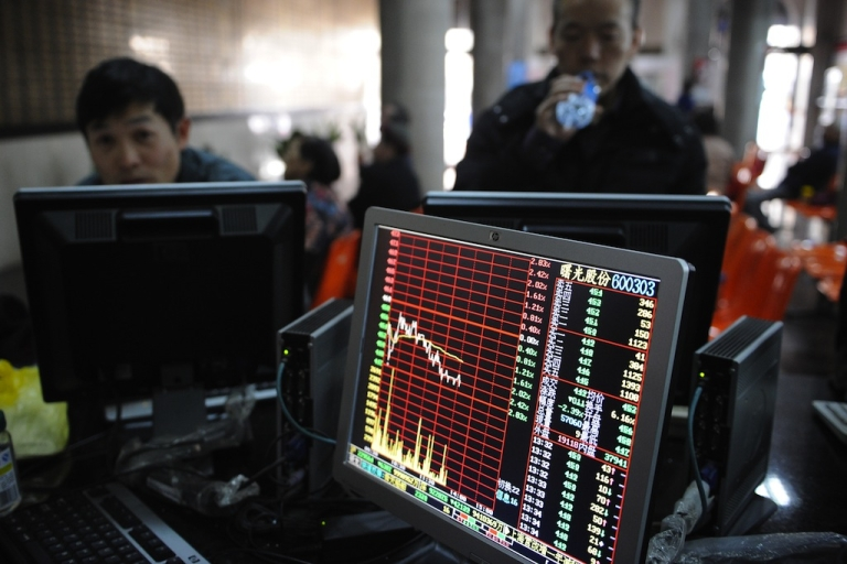 <p>Investors look at stock prices on a screen at a securities exchange in Shanghai on March 4, 2013.</p>