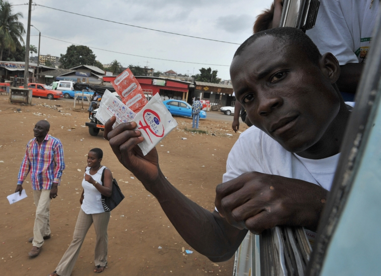 <p>A man shows condoms from a bus window at the start of a road campaign in Yopougon, a working district of the capital city Abidjan on September 28, 2009, as part of an AIDS prevention programme for 5 millions people on an Abidjan-Lagos axis including five West African countries: Ivory Coast, Ghana, Togo, Benin and Nigeria</p>