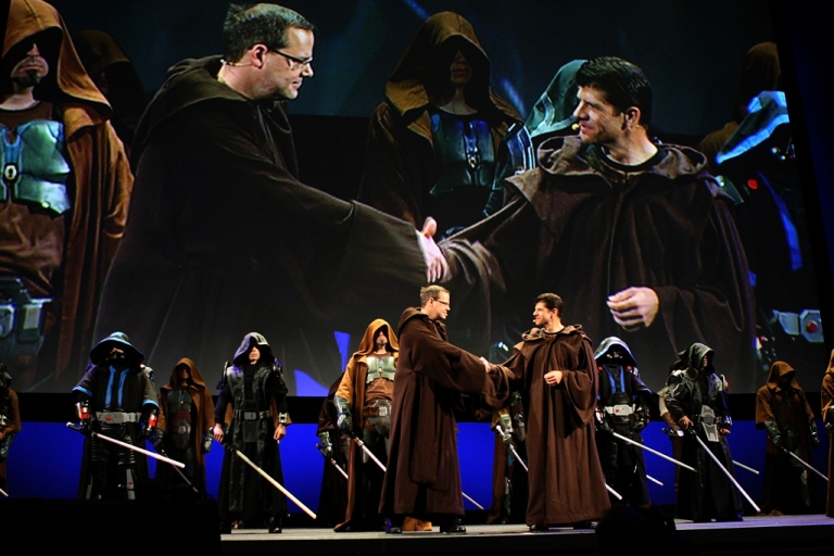 <p>BioWave co-founder Dr. Ray Muzyka, left, and LucasArts president Darrell Rodriguez join characters wearing robes and wielding lightsabers on stage to promote their joint effort, Star Wars: The Old Republic, on June 1, 2009 in Los Angeles, California during the E3 Expo.</p>