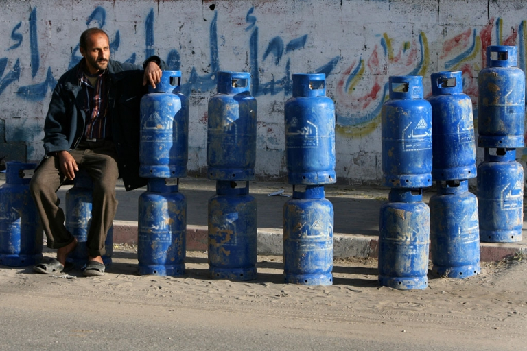 <p>A Palestinian man sits with cylinders of cooking gas, smuggled into the Gaza Strip from Egypt through a tunnel, that he is selling on a street in Gaza city.</p>