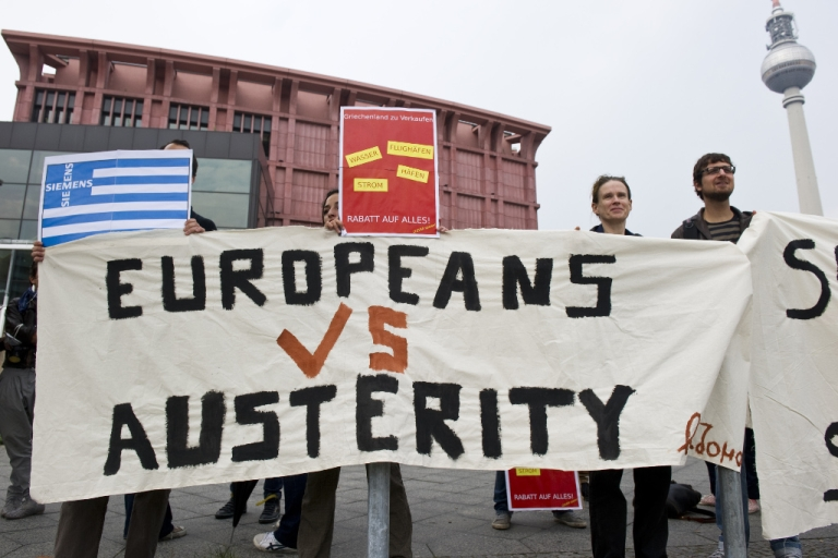 <p>Greek activists display a banner reading 'Europeans vs austerity' as they stage a protest opposite the venue of a meeting of the Federation of German Industry in Berlin September 27, 2011.</p>