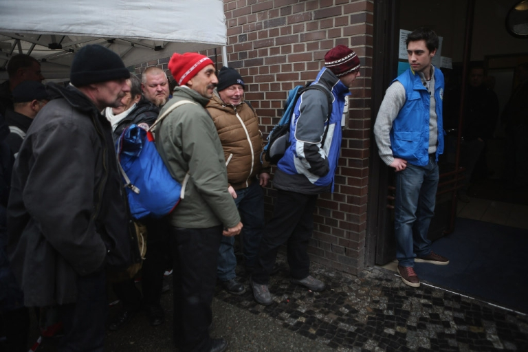 <p>Visitors, mostly homeless men, wait outside the Bahnhofsmission Protestant charity facility for a free lunch as theology student and volunteer Markus (R) prepares to let them in at Zoo train station on February 20, 2013 in Berlin, Germany. Both poverty and pensions that have not kept up with the rising cost of living will be contested topics in federal elections scheduled later for this year.</p>