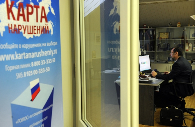 <p>A picture taken through a glass window shows a staffer of Russia's leading independent election watchdog Golos working at the monitoring body's office in Moscow on December 2, 2011. Golos was fined for refusing to comply with Russia's new law on NGOs on April 26, 2013.</p>