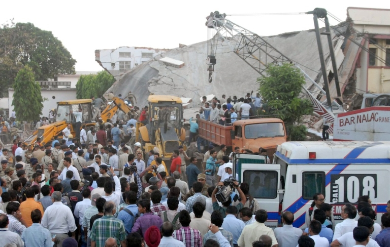 <p>Onlookers and rescue personnel are pictured at the scene of a hospital collapse in Bhopal on April 26, 2013. Up to 15 people, mostly patients, were feared trapped after part of a hospital roof caved in on Friday in the central Indian city of Bhopal, officials and eyewitnesses said.</p>