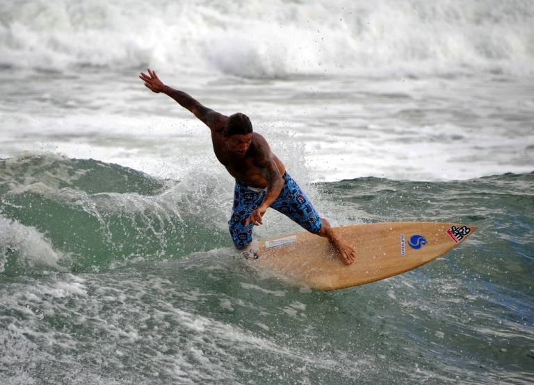 <p>A man surfs at Kuta beach on Indonesia's resort island of Bali on May 18, 2012.</p>