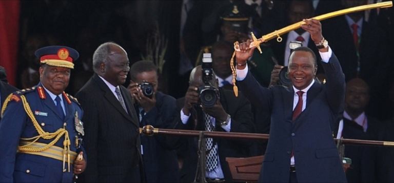 <p>Kenya's 4th President Uhuru Kenyatta receives a symbolic sword of power from outgoing president Mwai Kibaki (2L) after he was sworn into office on April 9, 2013 in Nairobi. Uhuru Kenyatta was sworn in as Kenya's fourth president on Tuesday to thunderous cheers from tens of thousands of supporters, despite facing trial on charges of crimes against humanity.</p>