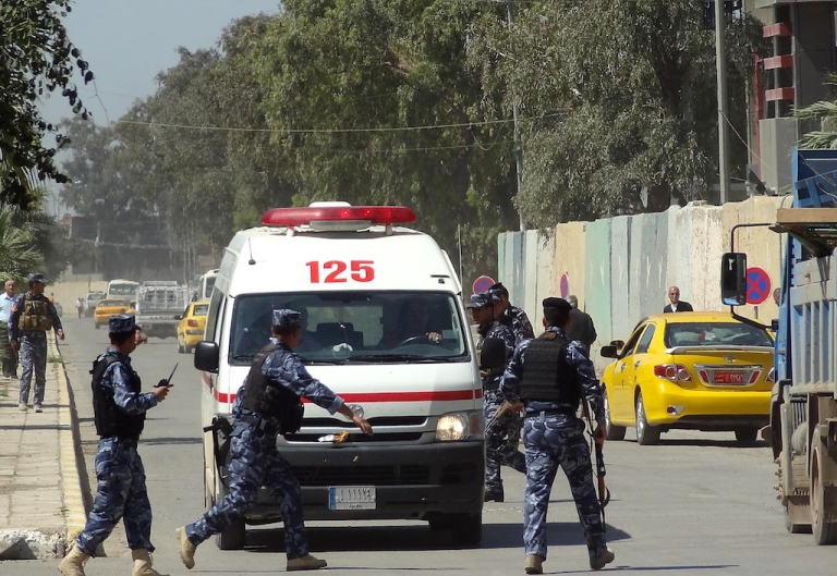 <p>Iraqi soldiers surround an ambulance as it arrives at a hospital following clashes between security forces and anti-government protesters, allegedly infiltrated by militants, on April 23, 2013 in Kirkuk.</p>