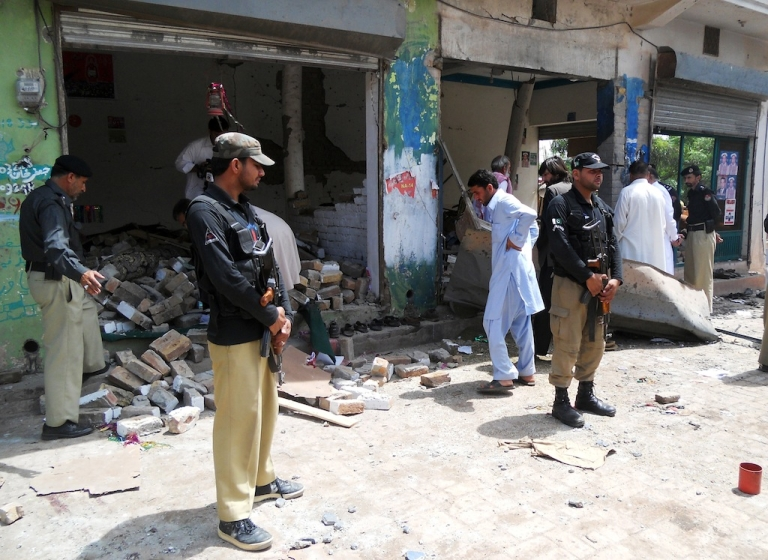 <p>Pakistani police officials examine a destroyed office of an election candidate fallowing a bomb attack in the city of Kohat on April 28, 2013.</p>