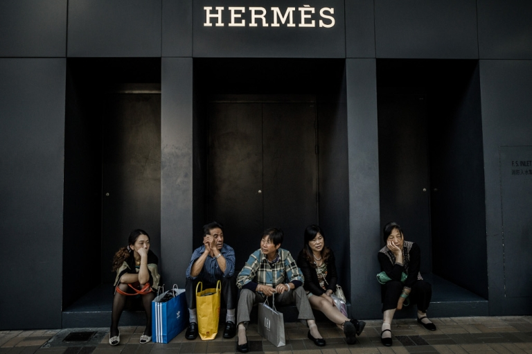 <p>Chinese visitors from the mainland sit in front of a luxury shop in Hong Kong on September 28, 2012.</p>