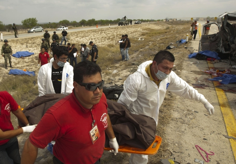 <p>Emergency rescue workers carry the body of one of the 10 members of La Reyna de Monterrey killed in a horrific traffic accident in northern Mexico on April 27, 2013.</p>