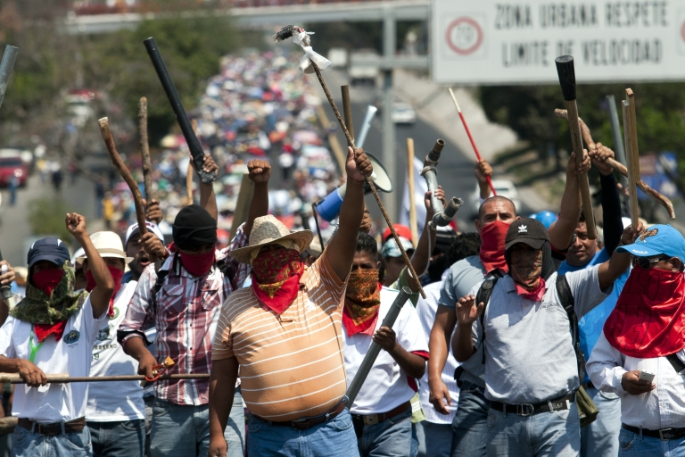 <p>Teachers and citizen vigilantes march in southern Mexico's Guerrero state in protest of national education reforms.</p>