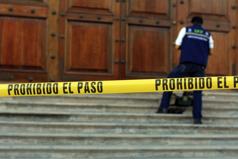 <p>Mexican federal police examine the entrance of the Mural newspaper in Guadalajara after assailants threw two explosive devices at the building in the early hours of April 17, 2013.</p>