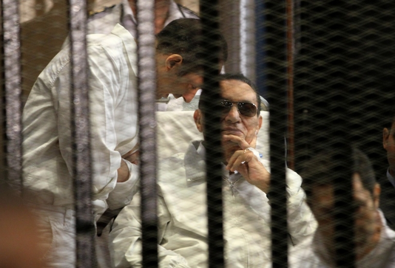 <p>Ex-Egyptian President Hosni Mubarak sits behind bars at the beginning of his retrial in Cairo on April 13, 2013. The presiding judge withdrew himself from the trial a few minutes after its opening.</p>