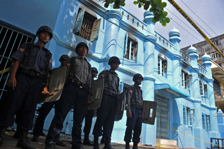 <p>Policemen stand guard in front of an Islamic school after a fire broke out at the school in downtown Yangon on April 2, 2013. A fire killed 13 students at a Muslim school in Myanmar's main city on April 2, police said, raising tensions in the wake of sectarian clashes despite police assurances that the blaze was accidental.</p>