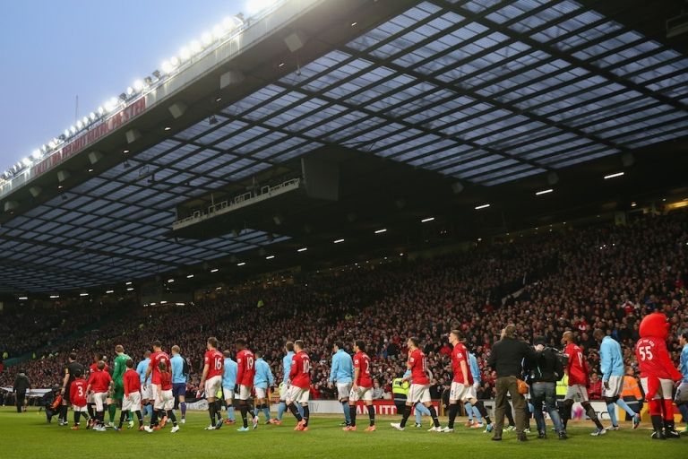 <p>Manchester United and Manchester City players walk out prior the Barclays Premier League match between Manchester United and Manchester City at Old Trafford on April 8, 2013 in Manchester, England.</p>