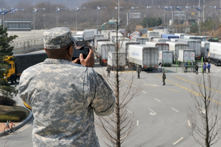 <p>A US soldier takes pictures as South Korean trucks return after being barred access to the Kaesong joint industrial park in North Korea on April 3, 2013.</p>