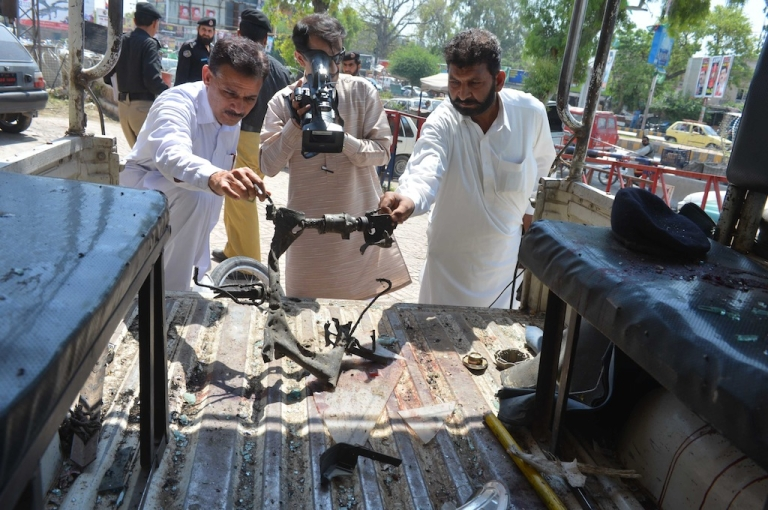 <p>Pakistani security personnel hold up a mangled section of a motorcycle to a media representative at the bomb blast site in Peshawar on April 29, 2013. A suicide bomber killed at least eight people and wounded 45 others when he rammed his motorcycle into a bus in Pakistan's northwestern city of Peshawar on Monday, police said.</p>