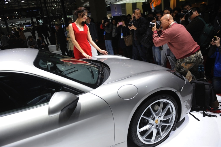 <p>A photographer takes photos of a model next to a Porsche on media day at the Shanghai auto show on April 20, 2013.</p>