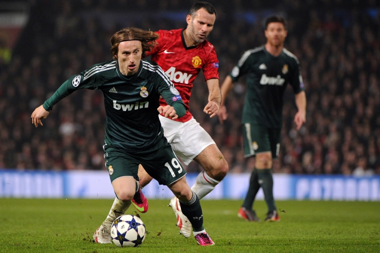 <p>Manchester United midfielder Ryan Giggs, center, chases Real Madrid's Luka Modric during the Champions League match in Manchester, England, on March 5, 2013. Real Madrid won 2-1.</p>