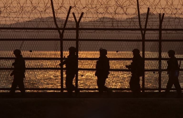 <p>South Korean soldiers patrol along a barb-wire fence near Dorasan on April 9, 2013 in Paju, South Korea.</p>
