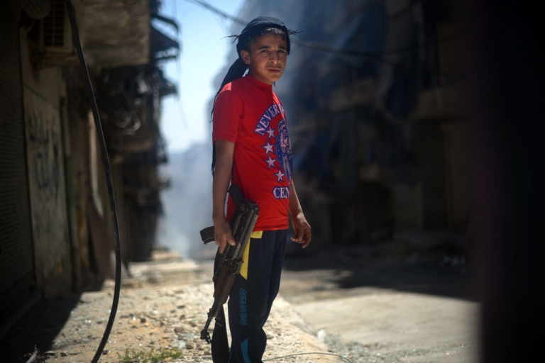 <p>A Syrian boy holds an AK-47 assault rifle in the majority-Kurdish Sheikh Maqsud district of the northern Syrian city of Aleppo. US intelligence agencies determined with