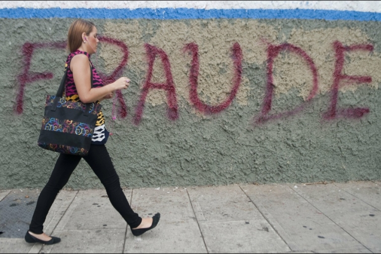 <p>A woman walks past a message painted on a wall in the streets of Caracas reading 'Fraud' as a protest against Venezuelan President Nicolas Maduro and the election result which gave him as the victor, on April 17, 2013.</p>