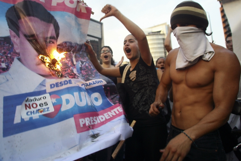 <p>Supporters of Venezuelan opposition presidential candidate Henrique Capriles burn a banner of new proclaimed President Nicolas Maduro in Caracas on April 15.</p>