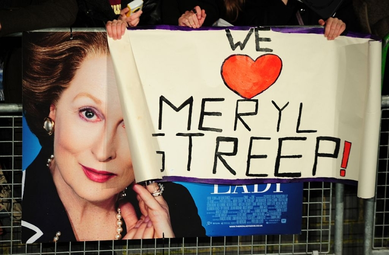 <p>A fan holds a poster reading 'We love Meryl Streep' over a poster promoting the European premiere of the film 'The Iron Lady' at BFI Southbank in London on January 4, 2012.</p>