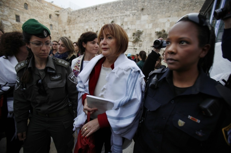 <p>Israeli policewomen detain a member of the liberal religious group Women of the Wall wearing a 'Tallit,' or traditional Jewish prayer shawl, at the Western Wall in Jerusalem's Old City on April 11, 2013.</p>