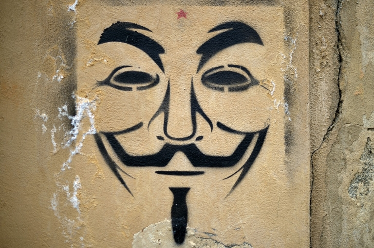 <p>A graffiti of Guy Fawkes mask, symbol of Anonymous, is pictured on April 6, 2013 in Florence. Designed by illustrator David Lloyd, it was used as a major plot element in V for Vendetta, published in 1982, and its 2006 film adaptation. After appearing in internet forums, the mask became the trademark symbol for the online hacktivist group Anonymous.</p>