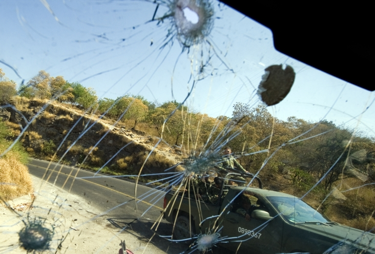 <p>Mexican Army soldiers passing by are seen through the bullet-riddled windshield of a truck in Apatzingan, Michoacan State, Mexico, on December 12, 2010. Mexican cartels have recruited US soldiers to carry out contract killing.</p>