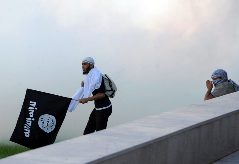 <p>A Tunisian protester holds an Al-Qaeda affiliated flag amid the smoke coming from the tear gas fired by riot police during a protest against a film mocking Islam outside the US embassy in Tunis on September 14, 2012.</p>
