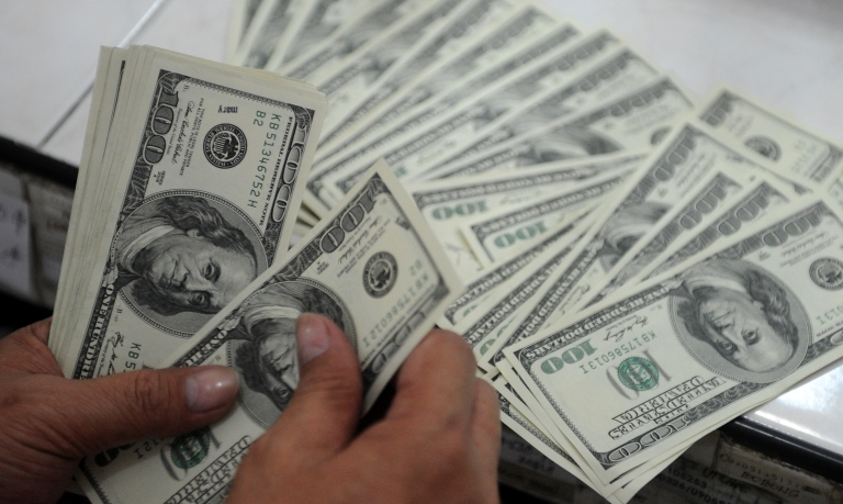 <p>An employee at a money changer counts USD 100 bills in Manila on October 25, 2012. Potentially millions of newly-minted $100 bills have been ruined.</p>