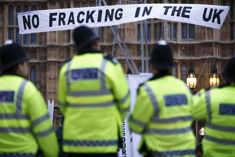 <p>British police secure the area where demonstrators erected a mock fracking rig with a banner reading 'No fracking in the UK' in a protest against hydraulic fracturing for shale gas outside the Houses of Parliament in London on December 1, 2012. UK Prime Minister David Cameron has come out in favor of fracking in the UK.</p>