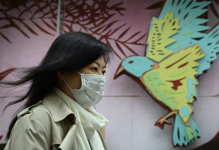 <p>A women wears a face mask as the city's commuters protect themselves against the H7N9 bird flu virus in the downtown area of Shanghai on April 16, 2013. New evidence shows that the virus can be spread by human-to-human contact.</p>