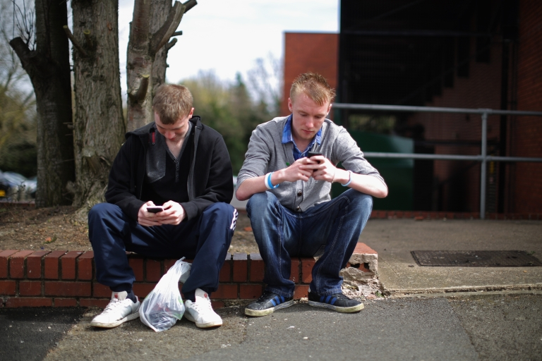 <p>Two youths send text messages on their smart phones in Corby, Northamptonshire, the youth unemployment capital of Britain, on April 24, 2013 in Corby, England. Young people in the UK are failing to find jobs at an alarming rate.</p>