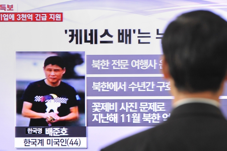 <p>A passerby watches a local television broadcast in Seoul on May 2, 2013 showing a report about Kenneth Bae, a Korean-American tour operator detained in North Korea.</p>