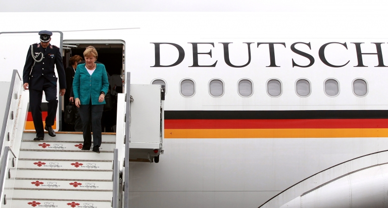 <p>German Chancellor Angela Merkel (R) disembarks from a plane on June 17, 2013. A man was recently arrested for breaking into a jet frequently used by Merkel and stripping down to his underwear. AFP PHOTO/POOL/ PETER MUHLY</p>